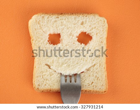 Happy toast with a fork in her mouth on a cutting board - stock photo