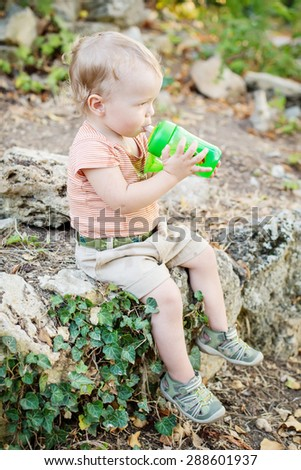 happy toddler boy drinks water sitting