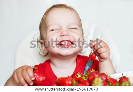 happy toddler boy eating strawberries on a white background - stock photo
