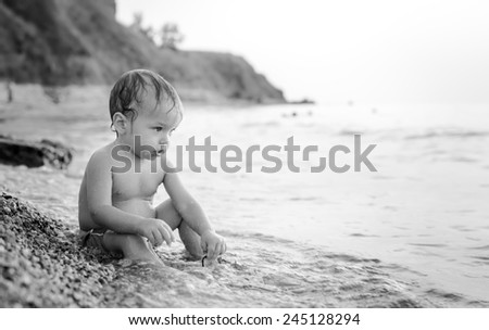Happy toddler boy playing on the sea at sunset ( black and white ) - stock photo
