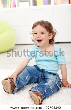 Happy toddler boy sitting on the floor laughing - stock photo