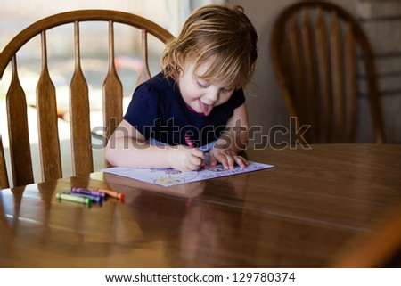 Happy toddler concentrating on coloring - stock photo