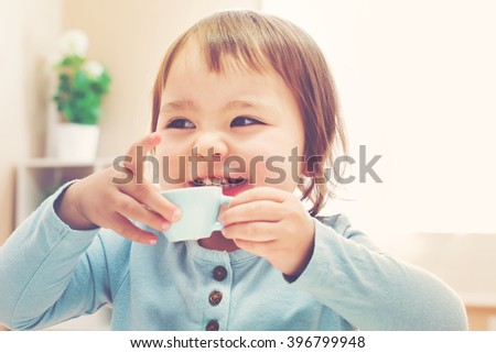 Happy toddler girl drinking from a tiny teacup - stock photo