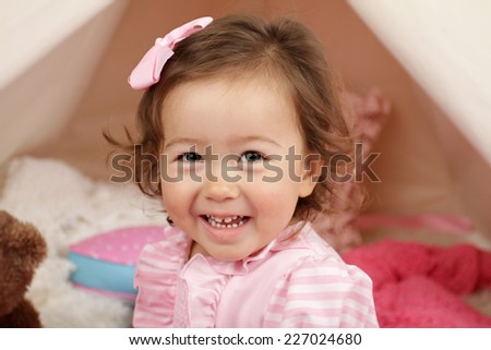 Happy toddler girl engaged in pretend play at home with a teepee tent - stock photo