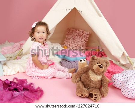 Happy toddler girl engaged in pretend play tea party indoors at home with a teepee tent - stock photo