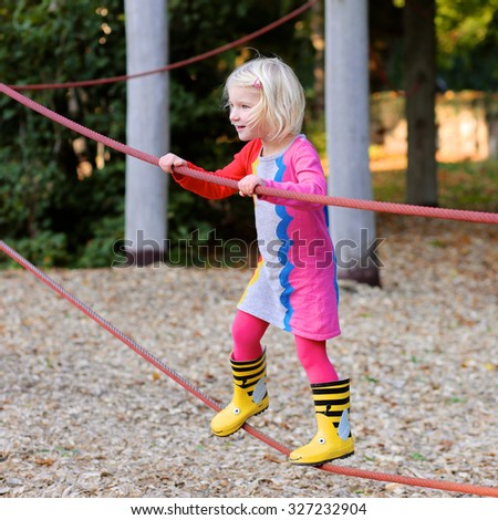 Happy toddler girl enjoying activity in the park. Adorable little child having fun outdoors climbing on playground on a sunny day - stock photo