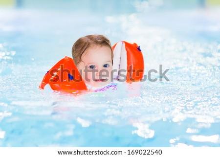 Happy toddler girl having fun in a swimming pool - stock photo