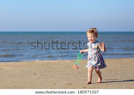 Happy toddler girl in beautiful dress running on the beach on a sunny summer day playing with colorful rainbow spring toy