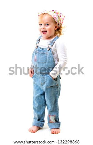 Happy toddler girl in overalls smiling - stock photo