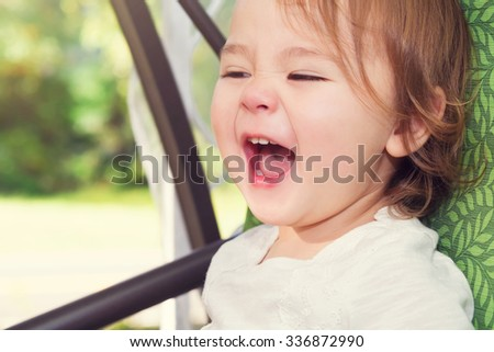 Happy toddler girl laughing while on a swing outside - stock photo