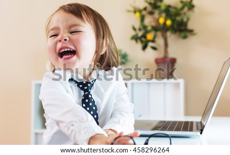 Happy toddler girl laughing while using her laptop - stock photo