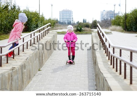 Happy toddler girl on a scooter in  park  - stock photo
