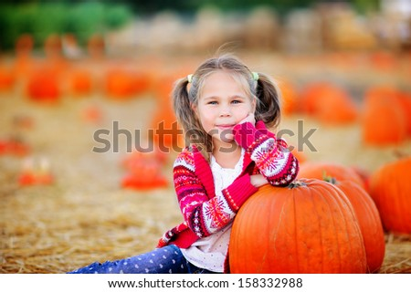 Happy toddler girl picking a pumpkin for Halloween - stock photo