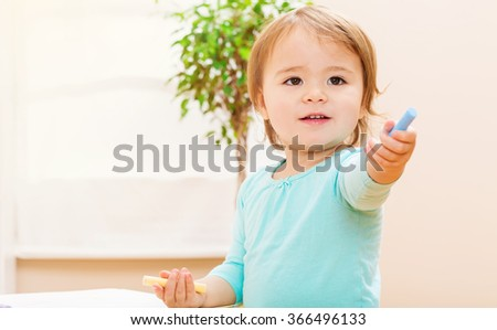 Happy toddler girl playing with chalk in her in house