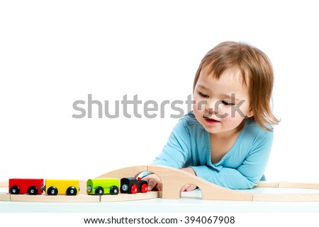 Happy toddler girl playing with colorful trains - stock photo