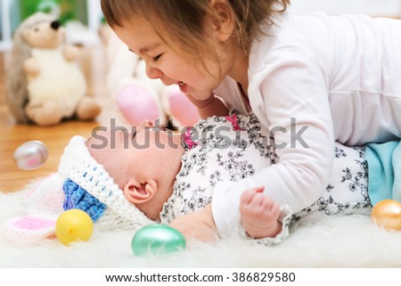 Happy toddler girl playing with her newborn baby sister on Easter - stock photo