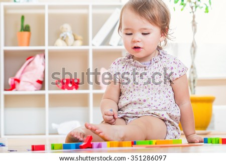 Happy toddler girl playing with her toys inside her house