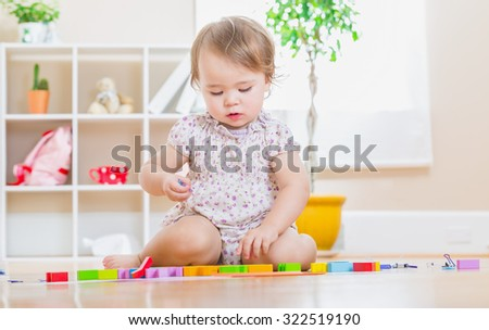 Happy toddler girl playing with her wooden toy blocks - stock photo