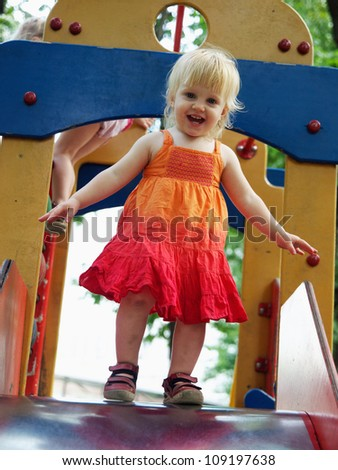 happy toddler girl ready to slide down - stock photo