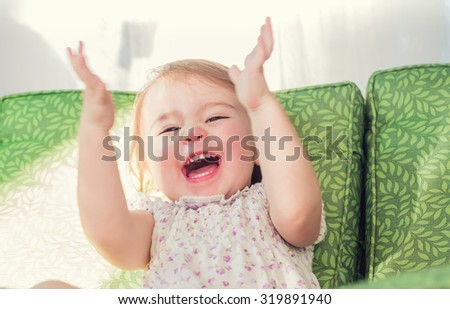 Happy toddler girl smiling and clapping her hands - stock photo