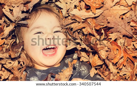 Happy toddler girl smiling while lying down in a big pile of leaves  - stock photo