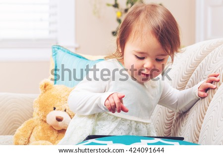 Happy toddler girl watching her tablet computer on her couch