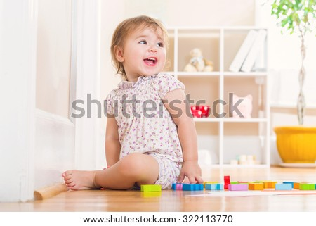 Happy toddler girl with a big smile playing with wooden toy blocks inside her house - stock photo
