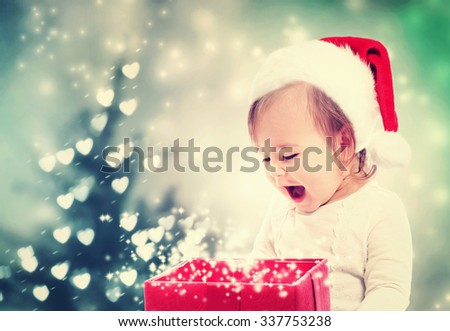 Happy Toddler girl with a Santa hat looking at Christmas present box - stock photo