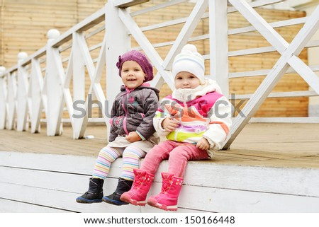 happy toddler girls sitting outdoors - stock photo