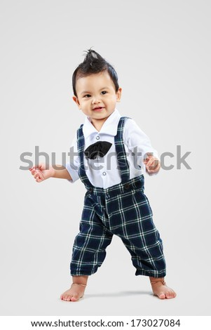 Happy toddler learning to walk - stock photo
