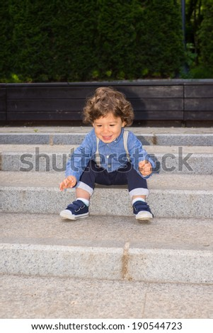 Happy toddler on stairs trying to get up