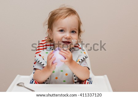 Happy toddler sitting in highchair and eating greek yogurt. Baby learning to eat and has yogurt on face. - stock photo