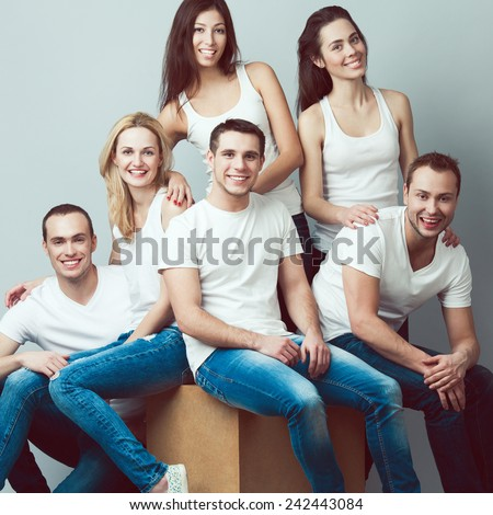 Happy together concept. Group portrait of healthy boys & girls in white t-shirts, sleeveless shirts and blue jeans standing, sitting, posing over gray background. Urban street style. Studio shot