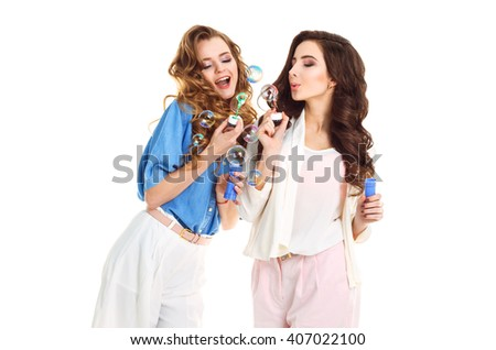 Happy together concept .two pretty girls blow bubbles on a white background . Vintage style. Fashion photo. studio photo . White background. smile face  - stock photo