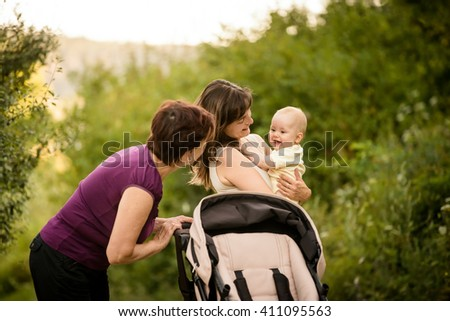 Happy together - grandmother with her daughter and her granddaughter outdoor in nature