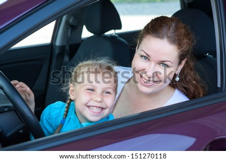 Happy toothy smiling mother with small daughter on driver seat inside of car - stock photo