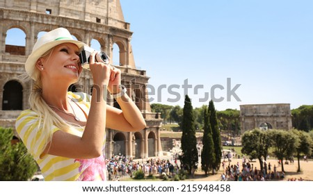 Happy Tourist and Coliseum, Rome. Cheerful Young Blonde Woman with Camera in Italy. Travel in Europe - stock photo