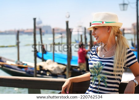 Happy Tourist and Gondolas in Venice, Italy. Cheerful Young Blonde Woman with Hat. Travel in Europe - stock photo