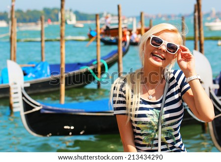 Happy Tourist and Gondolas in Venice, Italy. Cheerful Young Blonde Woman with Sunglasses. Travel in Europe  - stock photo