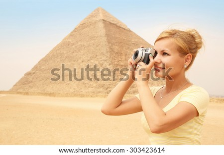 Happy Tourist and Pyramid, Cairo, Egypt. Cheerful Young Blonde Woman with Camera in Giza