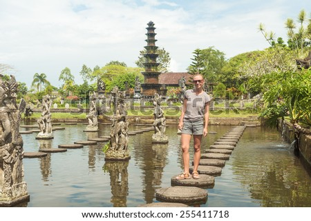 Happy tourist at Tirtagangga water palace with fountains  and ponds on Bali, Indonesia - stock photo