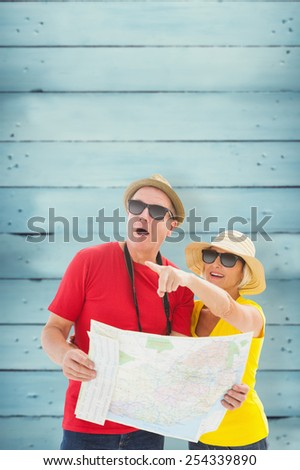 Happy tourist couple using map against wooden planks