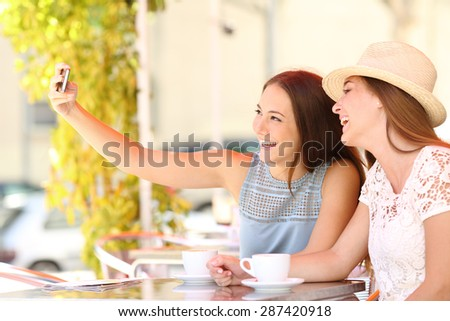 Happy tourist friends taking a selfie photo with smartphone in a coffee shop terrace - stock photo