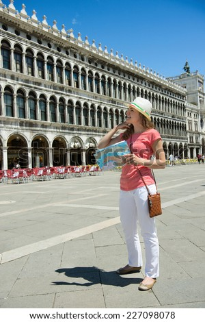 Happy tourist girl with map at San Marco square in Venice - stock photo