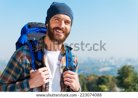 Happy tourist. Handsome young man carrying backpack and looking at camera with smile while standing in the nature - stock photo