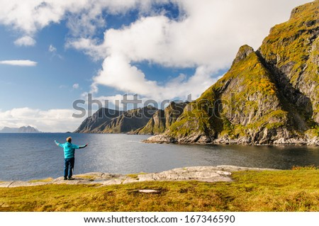 Happy tourist on the coast of fjord with stunning mountains on Lofoten islands in Norway - stock photo