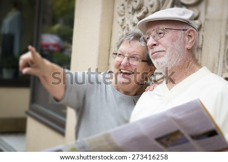 Happy Tourist Senior Couple Looking at Brochure Map. - stock photo
