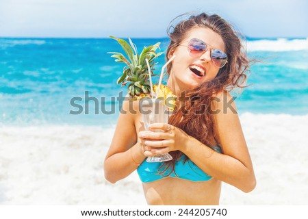 happy tourist woman holding a cocktail in her hands on a beach - stock photo