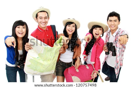 Happy tourists pointing to camera and one holding the map - stock photo