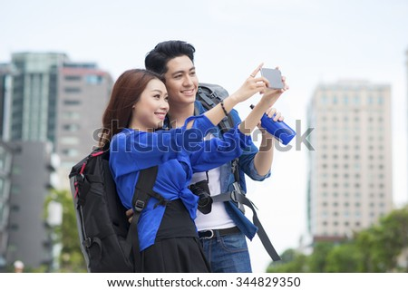 Happy tourists taking photo of themselves. summer holidays, travel, vacation, tourism and dating concept - couple taking photo picture with camera - stock photo